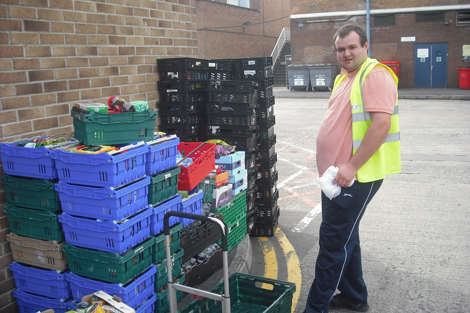 Trainee working at a foodbank, loading up boxes of donated goods