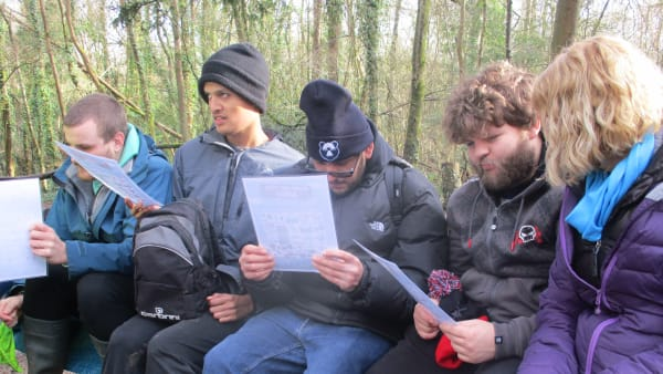 Group photo of trainees reading instructions on a woodland skills project
